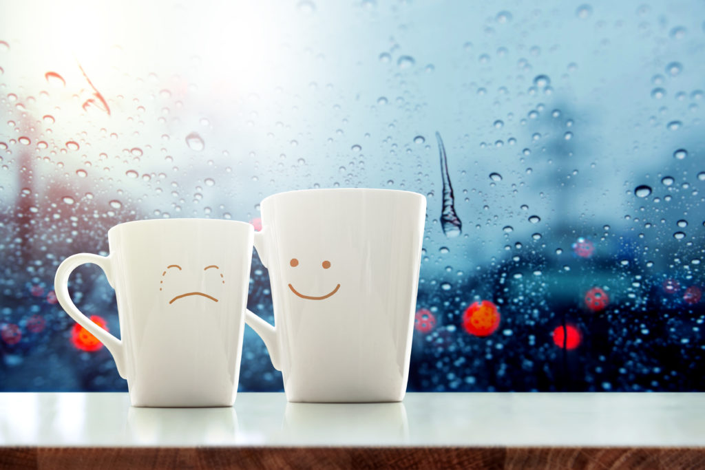"""It's ok"" concept, Friend of  Coffee Mug with Sadness crying face cartoon and kindness happy face inside the room, Blurred city light and rain drop in city as outside view through glass window"