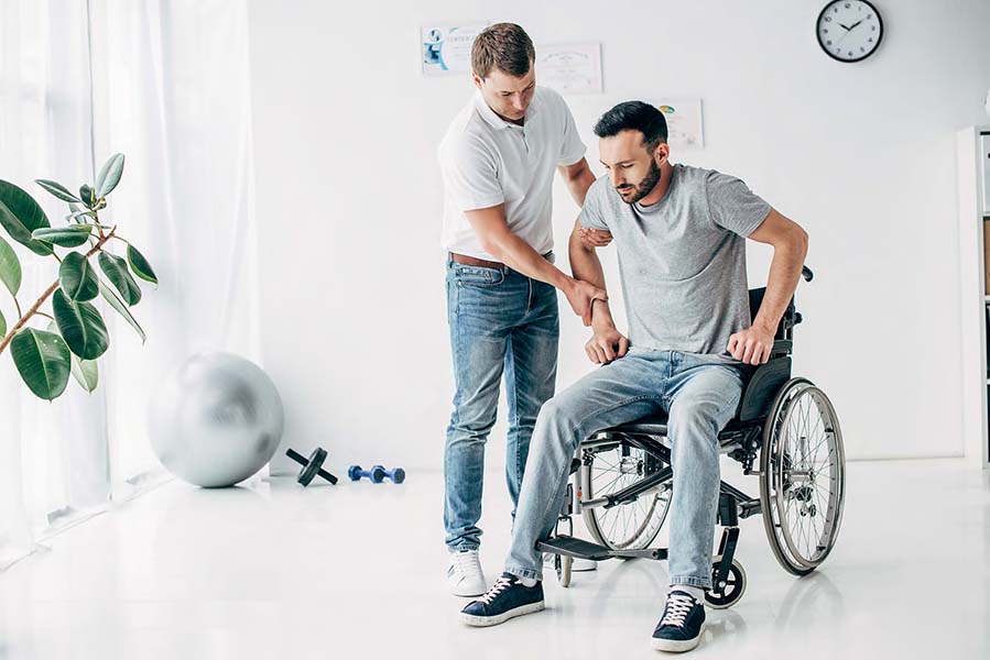 Physiotherapist helping man in Wheelchair during recovery in hospital